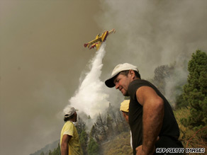 Volunteers look on as a plane drops water on wildfires in La Palma Sunday.