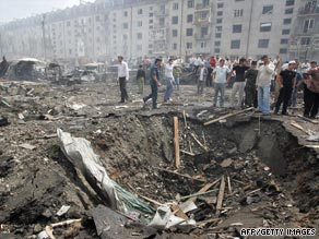 People stand near a crater caused by the blast in Nazran.