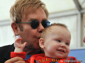 Elton John kisses baby Lev during his visit to the orphanage in Ukraine on Saturday.