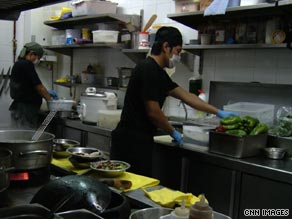 Kitchen staff at Silk and Soya restaurant in Spain wear face masks and gloves while preparing food.