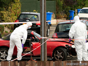 Bomb disposal experts examine a car Friday after a blast beneath it in east Belfast, Northern Ireland.