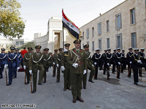 An Iraqi honor guard parades outside the former palace of Saddam Hussein in Baghdad on Thursday.
