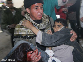 A wounded Palestinian baby is carried into the Al-Shifa hospital Sunday in Gaza City.