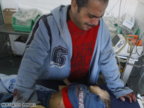 A man weeps over his dead child at a Gaza hospital Monday.
