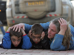 An Israeli woman and her two children take cover during a rocket attack alert near Kfar Aza.