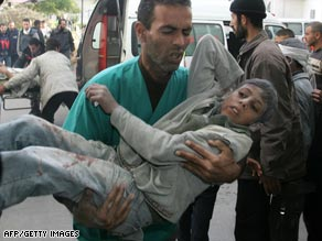 Palestinians carry a boy wounded in an Israeli military strike to hospital on January 14.