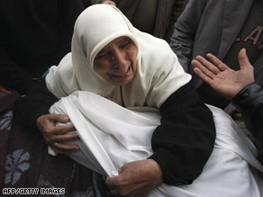 A woman cries as she holds the body of one of her relatives at the mortuary of Al-Shifa hospital on Friday.