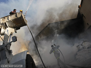 Firefighters try to douse a fire Thursday at the United Nations' main relief agency in  Gaza City.