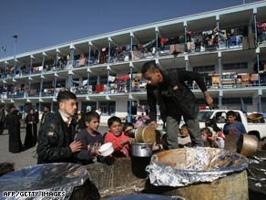 Palestinians who fled their homes during Israel's offensive receive food in a refugee camp in Gaza on January 15.