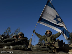 An Israeli soldier holds up an Israeli flag after leaving Gaza on Sunday.