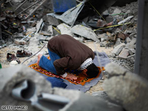 A Palestinian man Monday prays in the rubble of his home,  destroyed during Israel's offensive in Gaza.