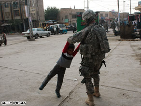 A U.S. soldier plays with a boy Monday while on patrol in Babil province, Iraq.