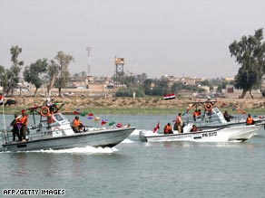 An Iraqi security patrols a water way in Basra.