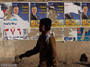 An Iraqi boy passes election posters Friday in Babil province. Provincial elections are set for January 31.