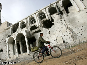 A Palestinian rides his bike near a mosque damaged during the attack by Israel on Gaza.