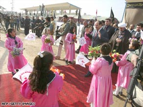 Surrounded by children and armed guards, Prime Minister Nuri al-Maliki campaigns in Hilla, Iraq.