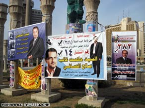 Iraqis stand near election posters Tuesday in Baghdad. Sunni Arabs say they plan to take part in the vote.