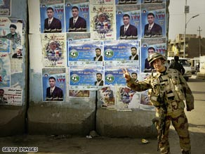 An Iraqi soldier stands next to elections posters on January 27, 2009, in Baghdad.