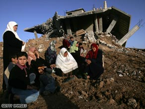 A Palestinian family sits Thursday amid ruins of their Gaza home, destroyed in Israel's strike against Hamas.