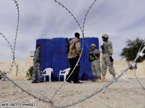 U.S. soldiers patrol a polling station in Diyala province, where two election workers were found dead Thursday.
