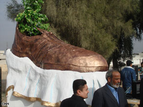 A monument to a shoe thrown at former President Bush is unveiled at the Tikrit Orphanage complex.