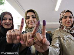 Iraqi women show off their ink-stained fingers after voting Saturday in Baghdad.