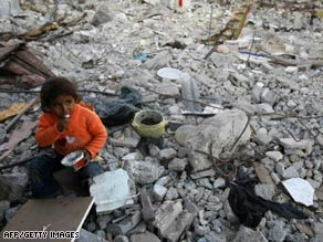 A Palestinian girl eats as she sits on the rubble of houses in Gaza on Wednesday.