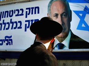 An orthodox Jewish man walks past a poster featuring Likud leader Benjamin Netanyahu.