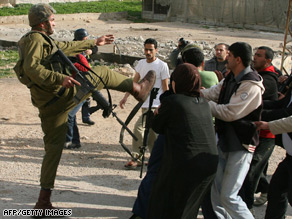 An Israeli soldier confronts Palestinian protesters during a demonstration Friday in the West Bank village of Jayyus.