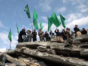Hamas supporters stand on the rubble of a building hit by an Israeli strike that killed Hamas' interior minister.