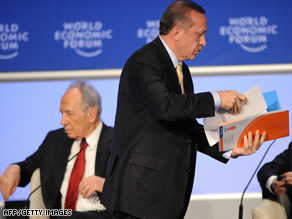 Recep Tayyip Erdogan leaves the stage at a conference last month as Shimon Peres sits, left.