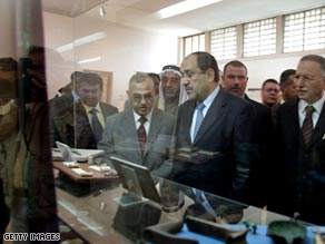 Iraqi Prime Minister Nuri al-Maliki (center) looks at antiquities displayed at Iraq's National Museum.