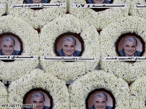 White wreaths with photos of Rafik Hariri at his tomb.