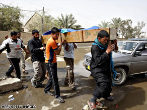 Iraqis carry a dead relative in Baghdad Sunday, the same day the U.S. said troop numbers in Iraq will drop by fall.