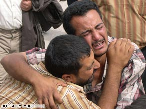 In April 2006, two Iraqis mourn a relative slain in sectarian violence in the city of Falluja.