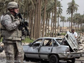 A U.S. soldier checks out the site of a car bomb attack Tuesday in a Shiite district of Baghdad.