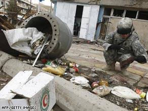 A U.S. soldier looks over debris after a suicide bombing Thursday in central Baghdad.