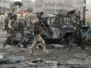 Iraqi soldiers survey one of the Baghdad marketplaces where car bombs detonated Wednesday.