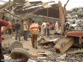 Iraqis look at damage from a bombing at a produce market in Baghdad on Wednesday.
