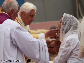 Pope Benedict XVI gives Communion to a Jordanian woman at a Mass in Amman, Jordan, on Sunday.