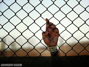 An Iraqi detainee grips a fence at Camp Cropper, one of the few U.S. detention centers remaining in Iraq.