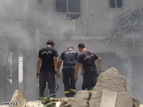Emergency workers at a destroyed building in Tyre, Lebanon, during the 2006 war