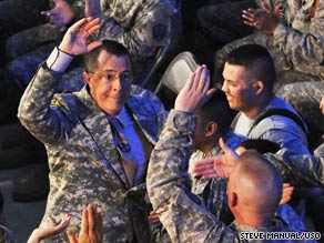 Stephen Colbert high-fives a serviceman after submitting to a military-style haircut in Iraq on Sunday.