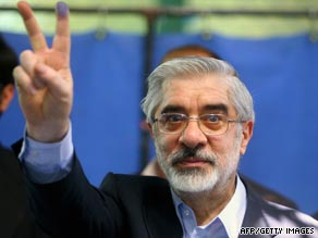 "Presidential candidate Mir Hossein Mousavi holds up the ""V"" sign after casting his vote on Friday."