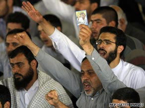 A man in the crowd holds up a photo of Ahmadinejad during Khamenei's address at Friday prayers.