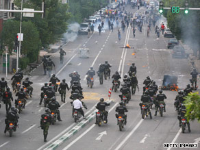 Protesters try to protect themselves from tear gas fired by police in Tehran.