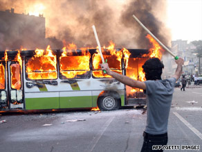 A demonstrator exults Saturday as flames consume a bus on a street in Tehran.