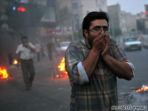 Protesters try to protect themselves from tear gas fired by police Saturday in Tehran.