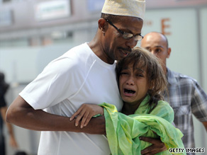 A man in Marseille hugs a relative of a passenger of the plane that crashed into the Indian Ocean.