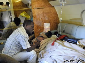 Bahia Bakari holds her father's hand as she lies on a stretcher in a plane after landing in France.